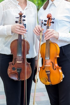 Девушка и женщина держат скрипки в руках