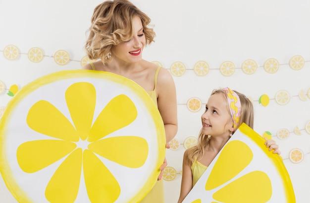 Девушка и женщина, держащая украшения ломтиками лимона
