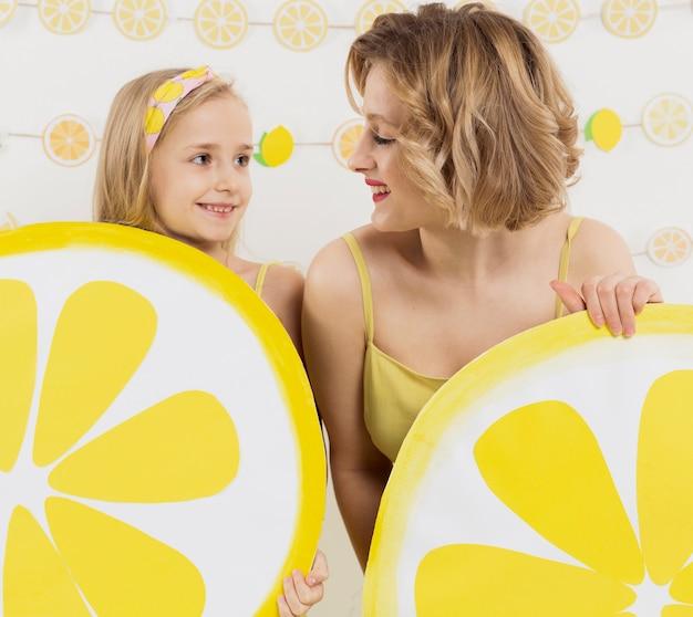 Девушка и женщина, глядя друг на друга, держа лимонный декор