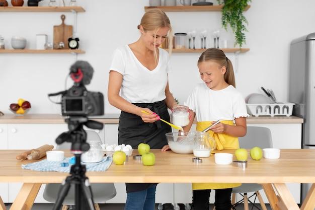 食べ物のミディアムショットを作る女の子と女性