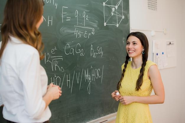 女の子は教育委員会の近くの先生に質問に答えます