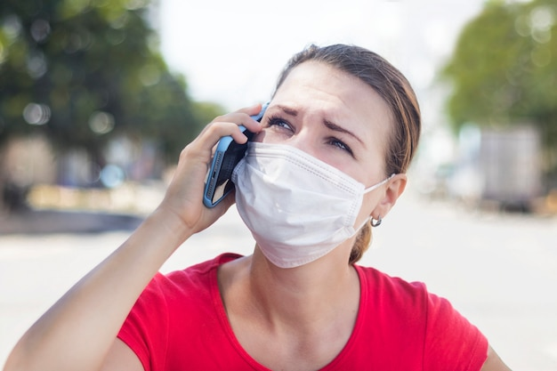 Girl, anxious woman in protective sterile medical mask on her face calling ambulance, need help, talking on cell mobile phone outdoors on asian street. virus, chinese pandemic coronavirus concept