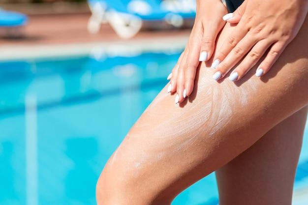 女の子は暑い夏の日にプールサイドで日焼けした脚に手で日焼け止めクリームを塗ります。休暇中の日焼け止めファクター、コンセプト。
