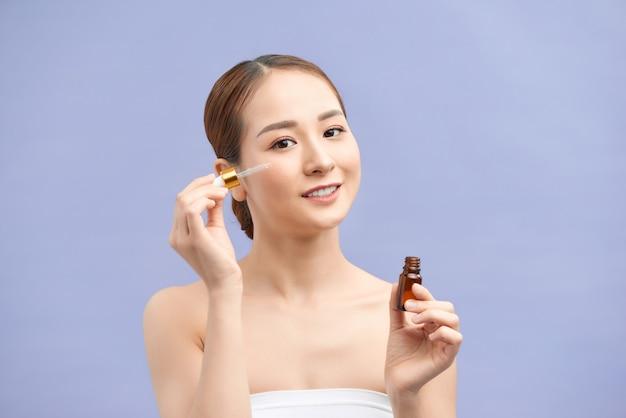 Girl applying eye serum isolated on violet