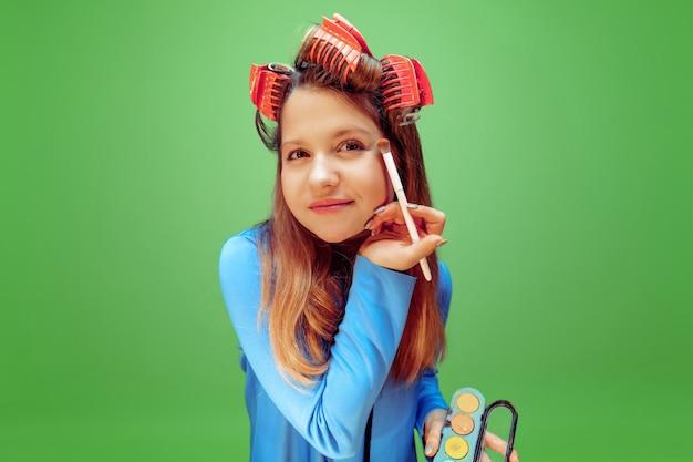 緑にアイシャドウを適用する女の子