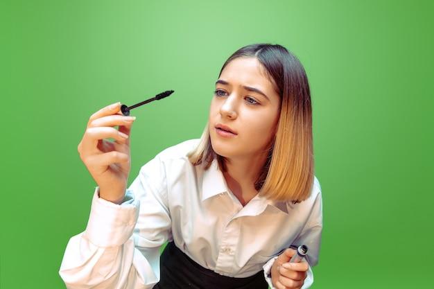 Girl applying mascara on green