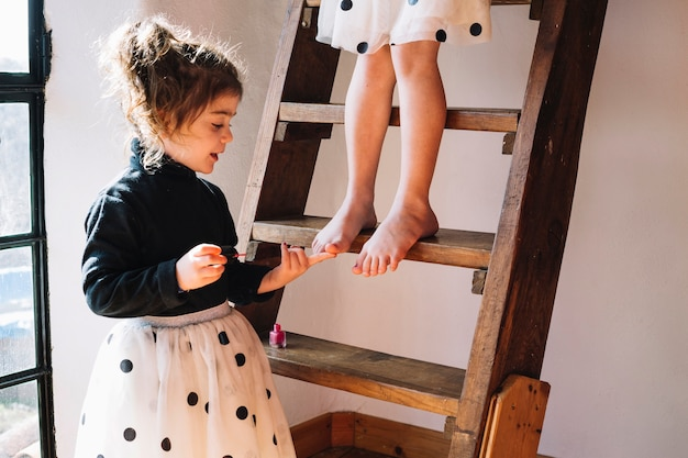 Girl applying nail polish on her sister's toe nails