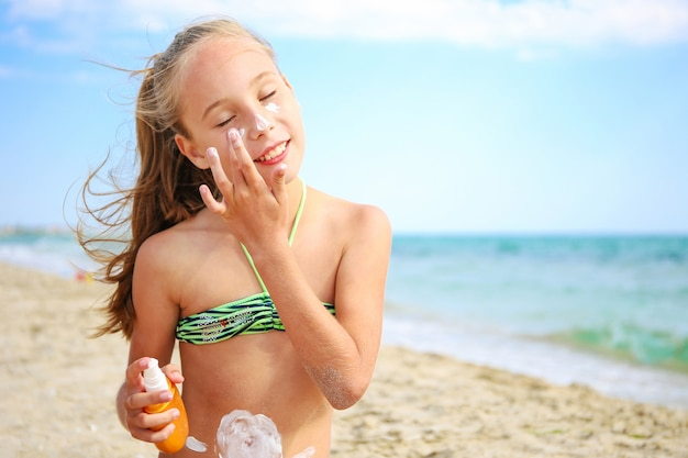 Girl applying protective sunscreen on face.