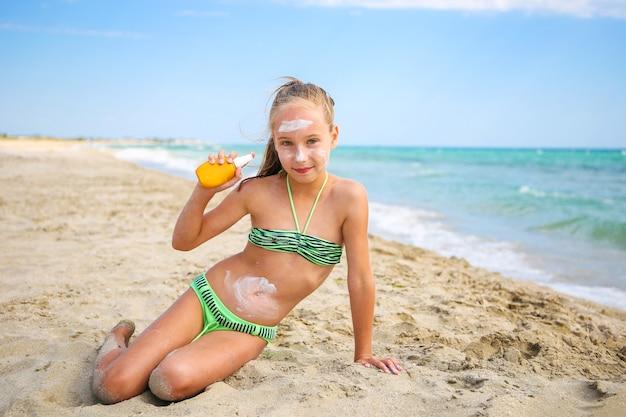 顔に保護日焼け止めを塗っている女の子。