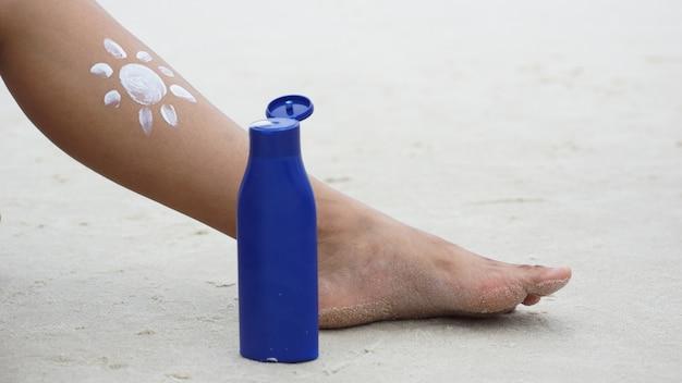 Girl applying sunscreen on her legs. skincare. body sun protection.