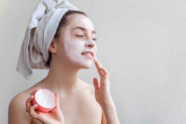흰색 배경에 고립 된 흰색 페이셜 마스크를 적용하는 소녀. 흰색 영양 마스크나 크림을 얼굴에 바르고 머리에 수건을 쓴 젊은 여성. 스킨 케어 트리트먼트 스파 자연의 아름다움과 미용 개념.