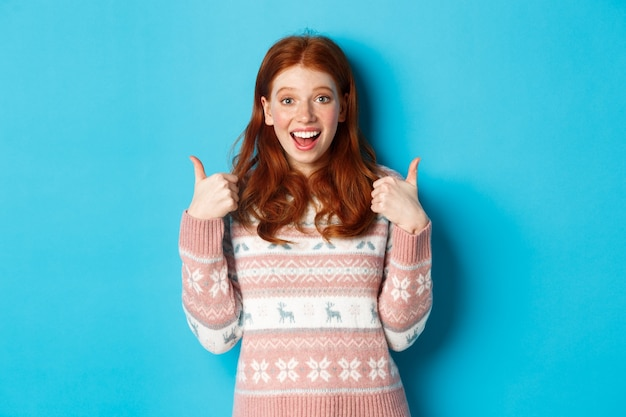 Girl approve something awesome, showing thumb-up, well done gesture and smiling amazed, standing over blue background.