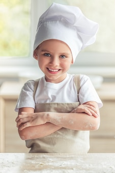 Girl in apron and chef hat is looking at camera and smiling.