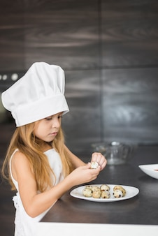 Girl in apron and chef hat peeling quail egg shell