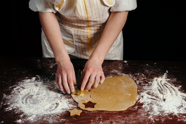 Girl in apron cuts dough cookies