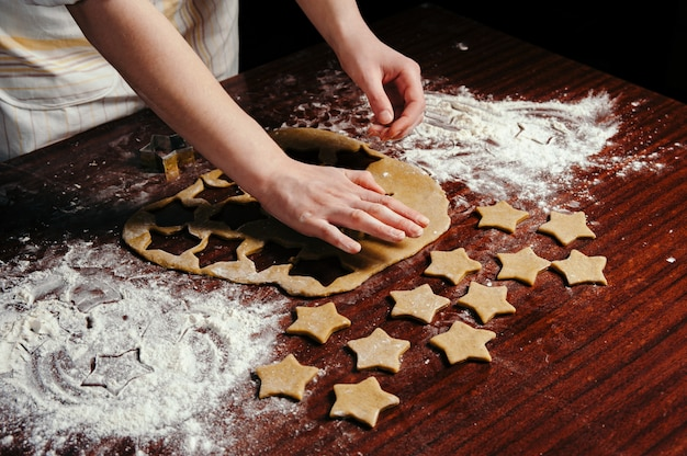 Girl in apron cuts dough cookies