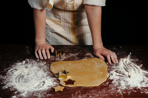 The girl in an apron cuts dough shaped cookies in the form of stars on a wooden table