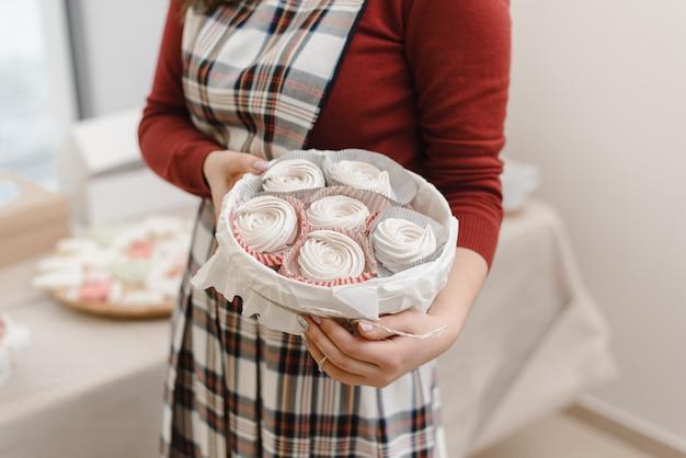 The girl in the apron holds the dessert meringue pavlova.