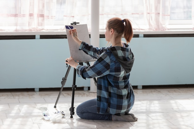 The girl artist is sitting on the floor of marble tiles. woman in the process of drawing oil paintings.