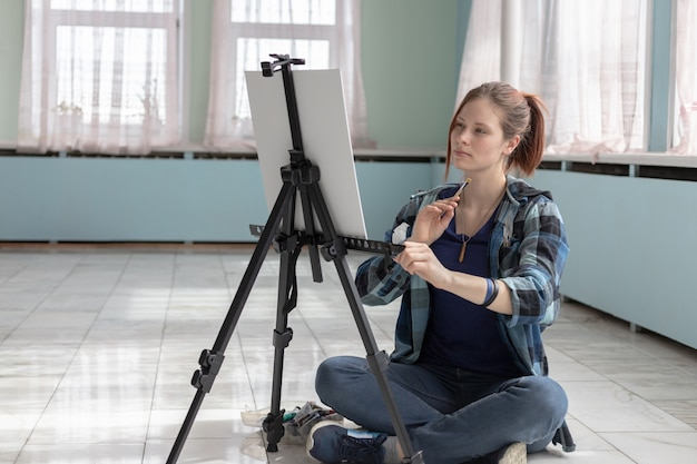 Girl artist paints with oil paints sitting on the marble floor. white canvas and easel stand on the floor of marble tiles in the room with turquoise and light green walls.