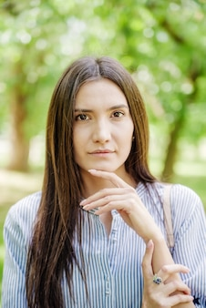 Girl of asian appearance in city park summer portrait of young tatar on background of green foliage