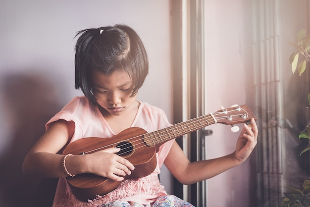 Girl asian appearance ten years playing ukulele in between studying music at the music