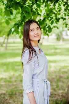 Girl of asian appearance on walk in city park. summer portrait