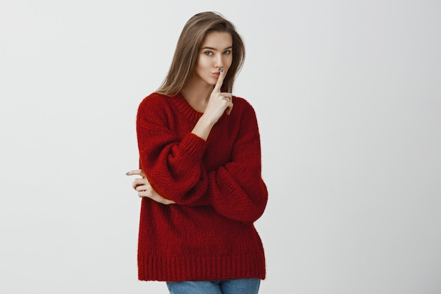 Girl asking friend to keep secret and told nobody. playful flirty european woman in stylish loose red sweater, holding index finger over mouth and smiling intriguingly, making shh or shush sign