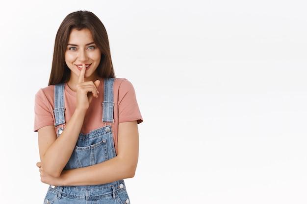 Девушка просит никому не рассказывать свой грязный секрет, загадочно хихикает и улыбается, прижимает указательный палец к губам, так как есть что скрывать, стоя на белом фоне готовит интересный сюрприз