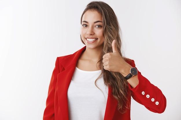 Девушка заверяет вас, что у вас удачный день. счастливая улыбающаяся великолепная женщина-предприниматель показывает палец вверх, одобряя потрясающую идею, рада дать положительный ответ, согласна, стоя у белой стены