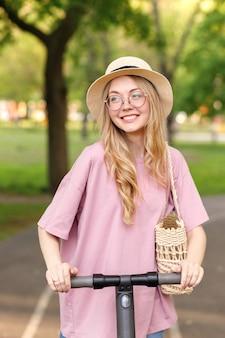 散歩の夏の電子スクーター公園の女の子