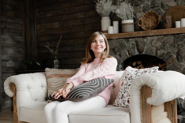 집에서 여자는 소파에 앉아 베개를 들고. 빈티지 스타일의 방. 집에서 쉬고 아름 다운 소녀입니다. 사랑스러운 여자의 초상화입니다.