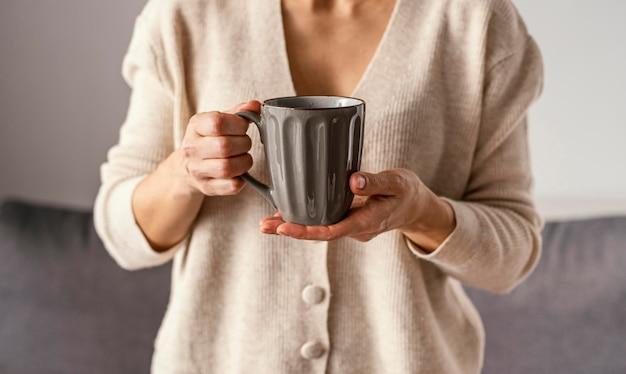 お茶を飲みながら家にいる女の子