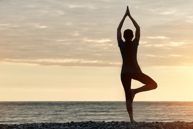 Девушка на закате практикует йогу на берегу моря, вид сзади