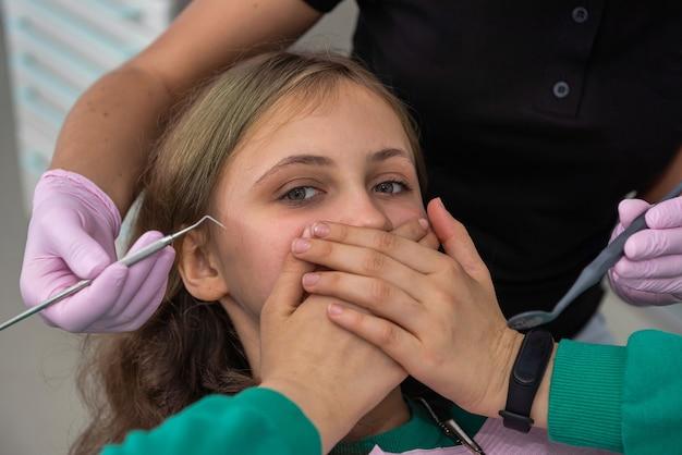 歯科医院の女の子が手で口を閉じる