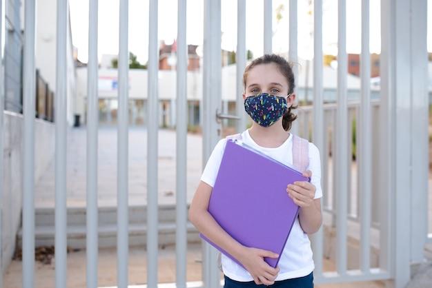 Девушка у дверей школы с маской в новой нормальной
