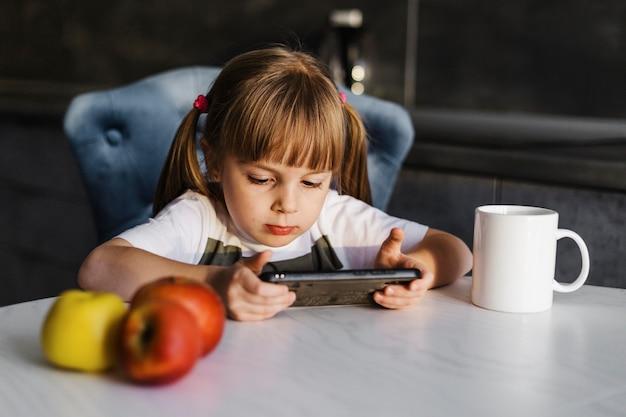 Девушка за столом, играя на мобильном телефоне