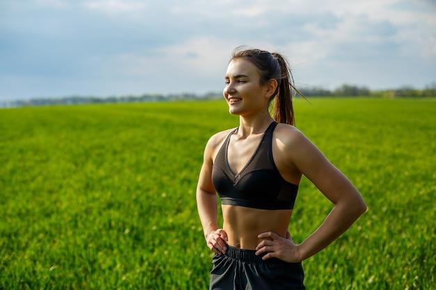 女子アスリートは屋外でウォームアップ、筋肉のエクササイズをします。若い女性は、スポーツ、健康的なライフスタイル、運動体のために行きます。彼女はスポーツウェア、黒のトップス、ショートパンツを着ています。スポーツのコンセプト。