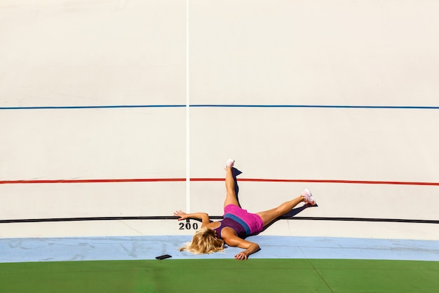 Girl athlete fell and lies on a treadmill