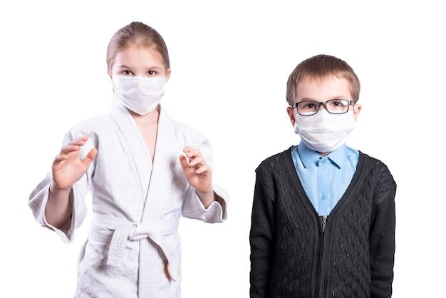 女の子アスリートはマスクを着用して男子生徒の男の子を抱きしめます。白い背景で隔離。高品質の写真