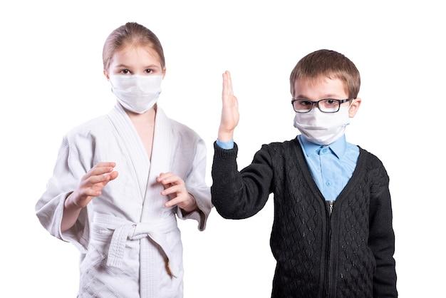 女子アスリートはマスクをかぶって男子生徒を抱きしめます。白い背景で隔離。高品質の写真