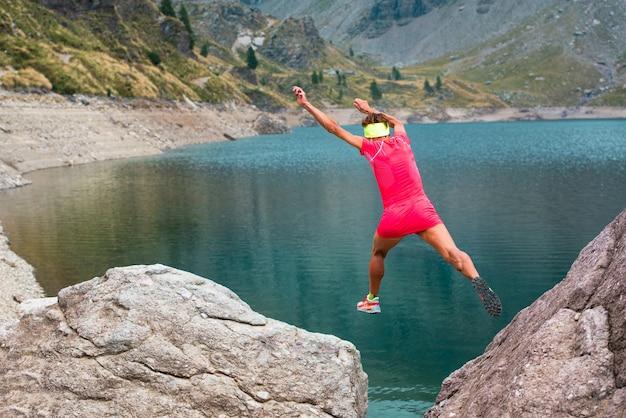 여자 선수는 고산 호수 근처의 유쾌한 자연 산에서 두 개의 바위 사이로 점프합니다.
