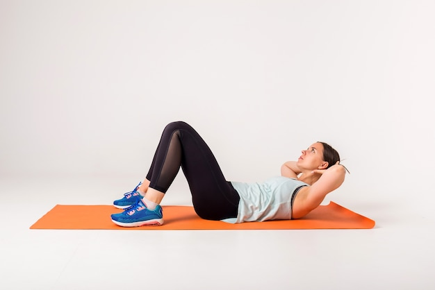 A girl athlete on an orange mat performs exercises for the press on a white isolated  with space for text