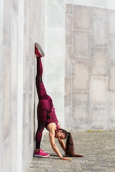 여자 선수는 신선한 공기에 벽에 기대어 체조 운동 꼬기를 수행