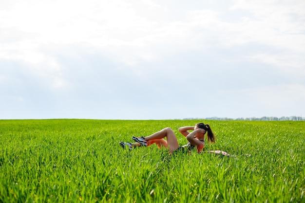 Девушка-спортсмен качает пресс, лежит на коврике на природе. молодая женщина занимается спортом, здоровым образом жизни, спортивным телом.