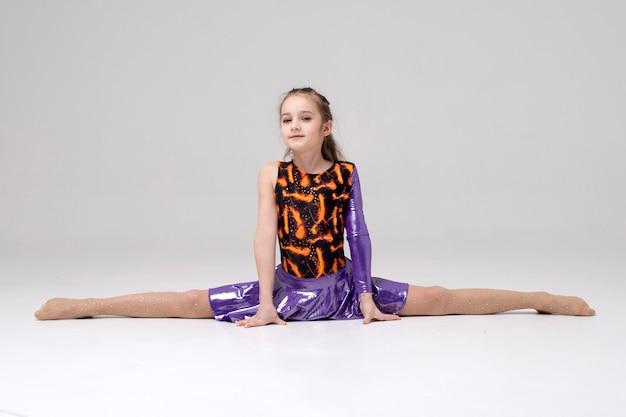 Девушка-спортсменка сидит на шпагате в гимнастическом купальнике