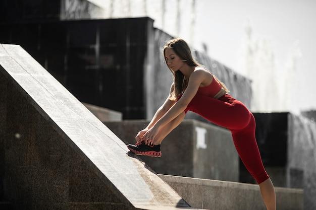 Girl athlete in sportswear tying shoelaces near the fountain
