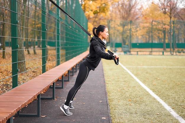 Девушка-спортсменка тренируется с использованием trx на спортивной площадке