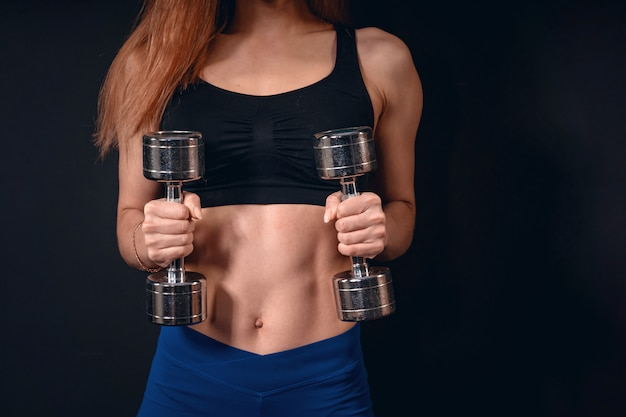 Girl athletic lifts dumbbell. exercise for biceps with dumbbells. with free text space.