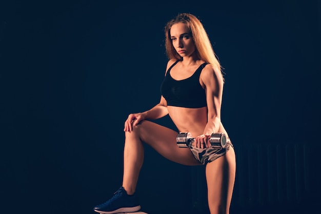 Girl athletic lifts dumbbell. exercise for biceps with dumbbells